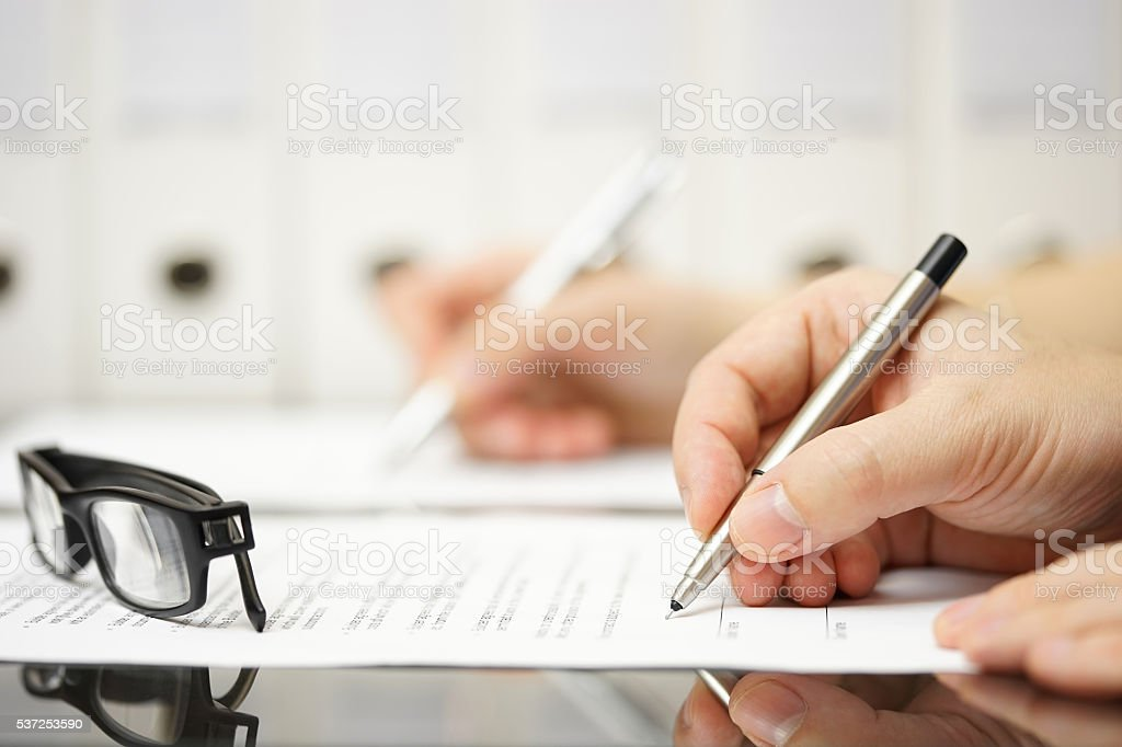 Business partners are signing contract after successful meeting stock photo