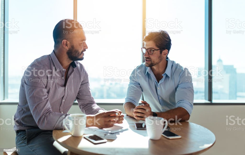Business partners discussing business plans sitting at table in office. stock photo