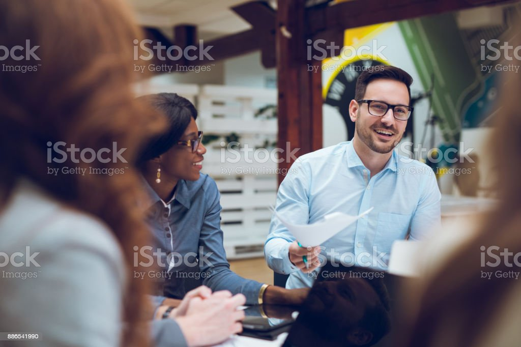 Business partners discussing documents and ideas at meeting stock photo