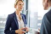 Senior businesswoman in discussion with male colleague during coffee break