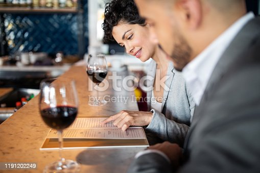 Two business people sitting at a bar counter. Businesswoman discussing menu with male partner.