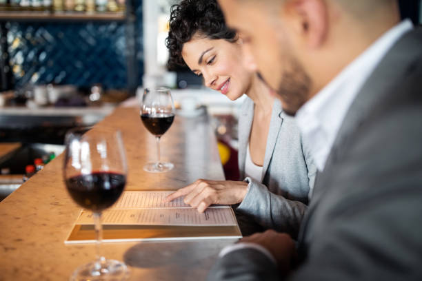 Business partners discussing menu at a bar counter stock photo