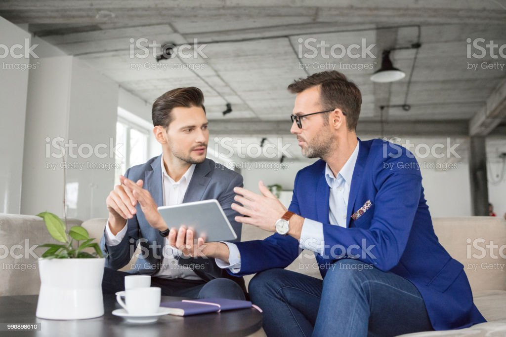 Business partners discussing new project Two businessman discussing new project on digital tablet in office lounge Adult Stock Photo