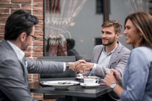 business partners greet each other in the cafe stock photo