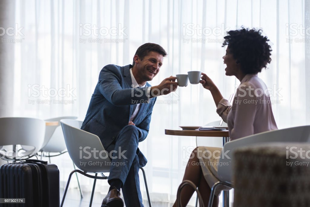 Business partners having coffee at airport cafeteria stock photo