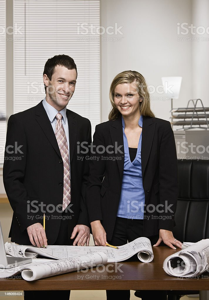 Business partners posing with blueprints royalty-free stock photo