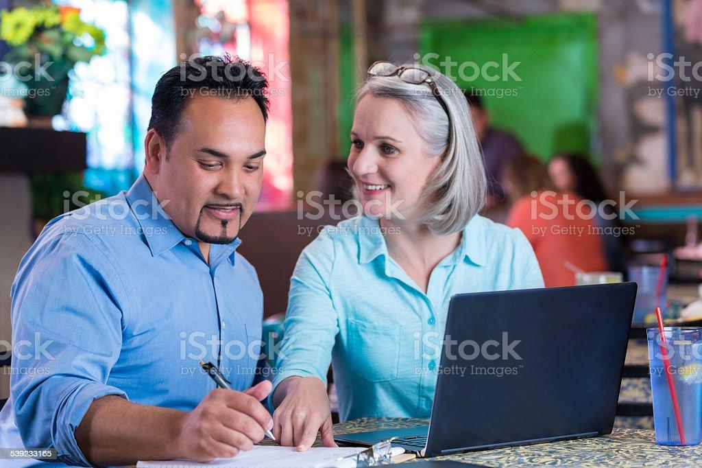 Socios de negocios de la revisión de la información financiera durante reunión en el restaurante foto de stock libre de derechos