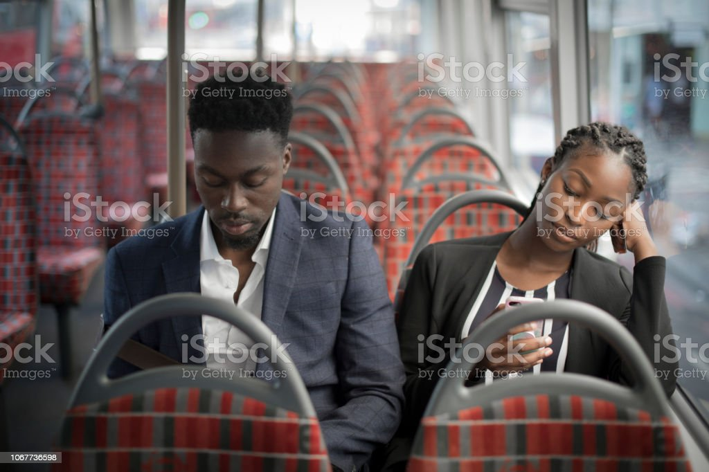 Business partners riding the bus to work stock photo