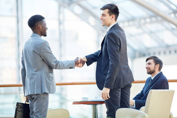 Business Partners Shaking Hands in Greeting Portrait of smiling successful businessman greeting African-American man in meeting shaking hands at table in office building foreign affairs stock pictures, royalty-free photos & images