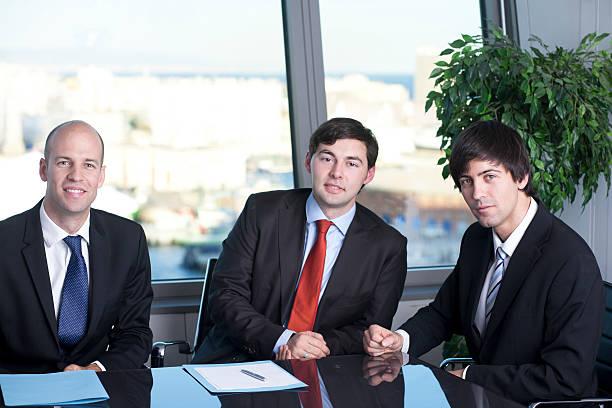 business partners smiling in office - four lawyers stockfoto's en -beelden