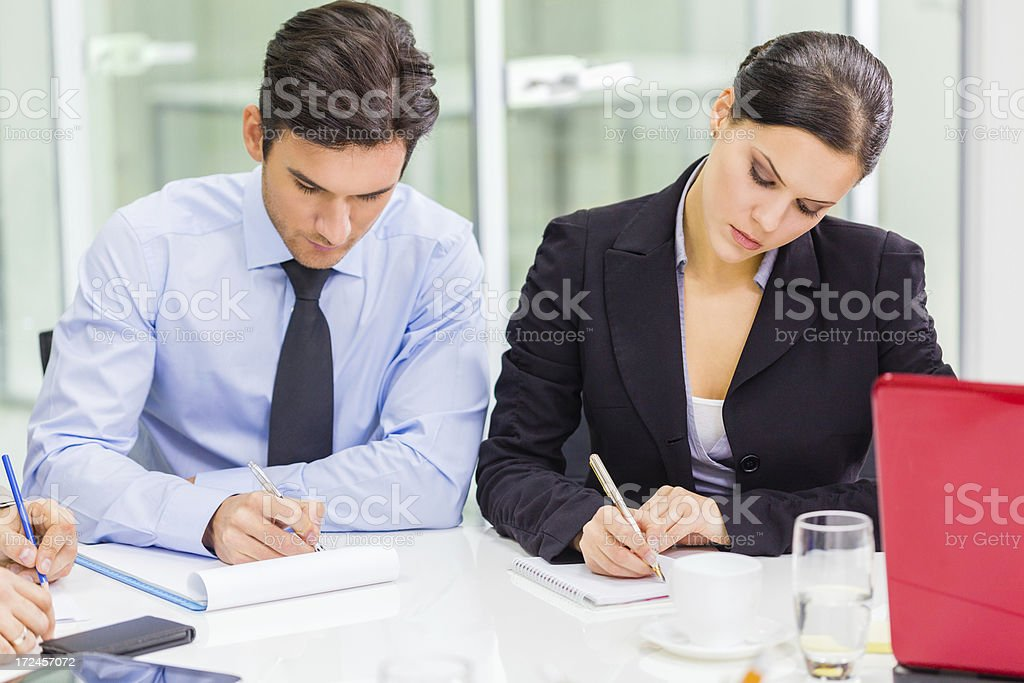 Business partners taking notes at a meeting royalty-free stock photo
