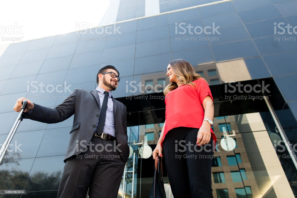 Business partners talking in front of large building stock photo