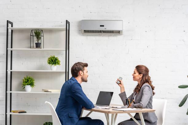 socios comerciales hablando mientras están sentados en el lugar de trabajo bajo aire acondicionado - foto de stock