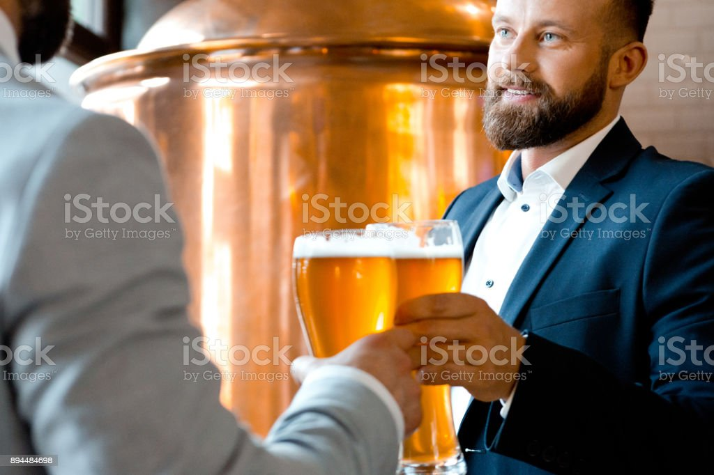 Business partners toasting beer during a meeting in brewery Two businessmen toasting beer in the microbrewery. Business partners toasting beer during a meeting in brewery. Adult Stock Photo
