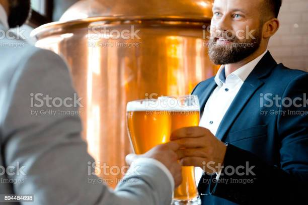 Business Partners Toasting Beer During A Meeting In Brewery Stock Photo - Download Image Now