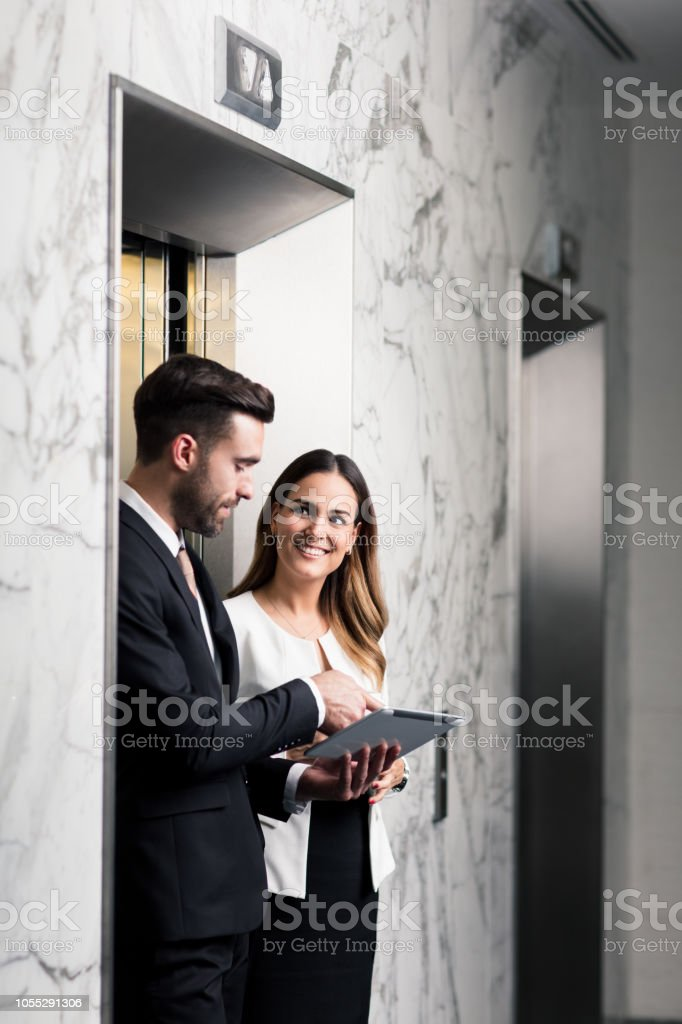 Business partners walking out of elevator with tablet stock photo