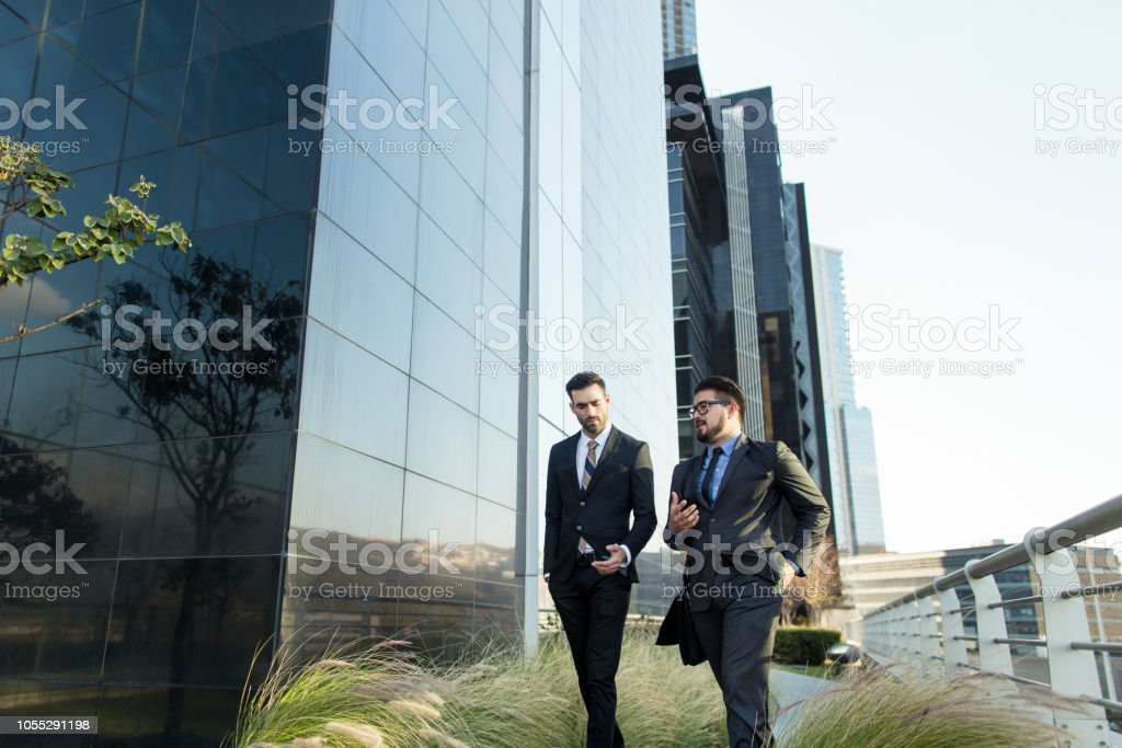 Business partners walking outside of large building stock photo