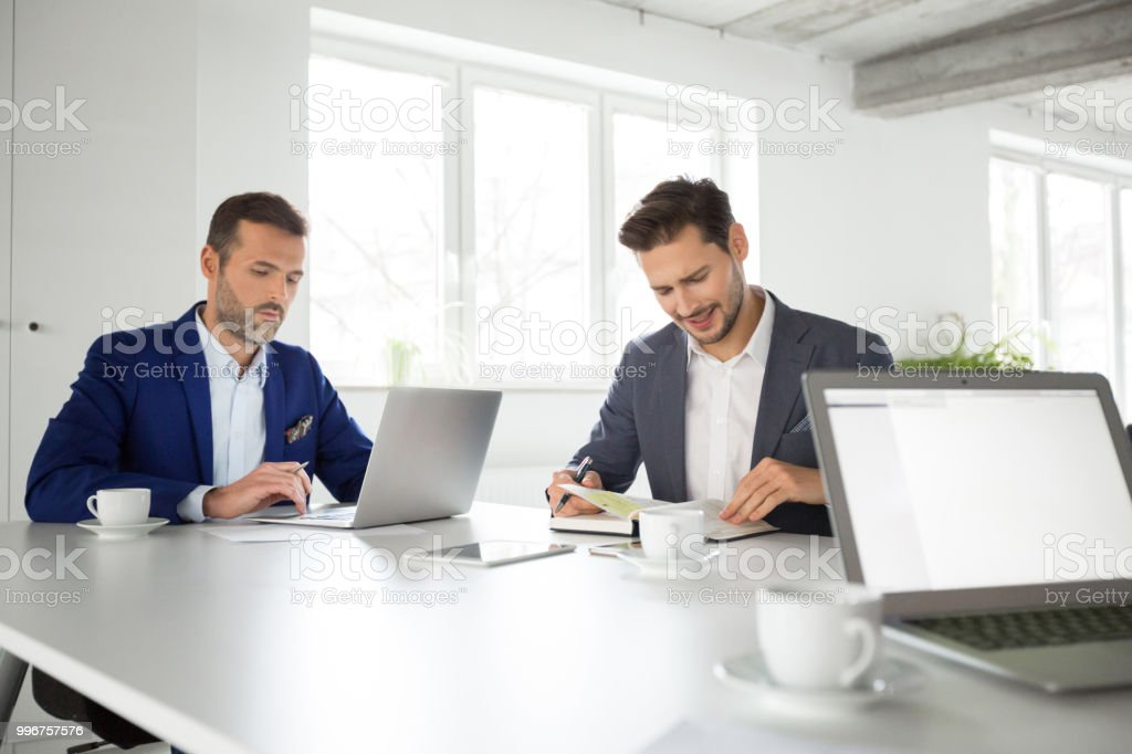 Business partners working together in office Two businessmen sitting at table and working. Business partners working together in office. Adult Stock Photo