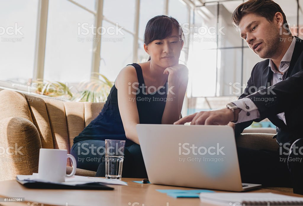 Business partners working together on laptop in office stock photo