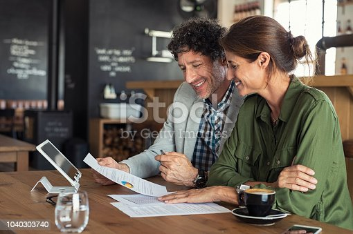 Portrait of mature business man and casual businesswoman sitting in cafe and discussing sales graph. Group of two middle aged coworkers working comparing forecasting graphics. Happy businessman reading report with his business partner.