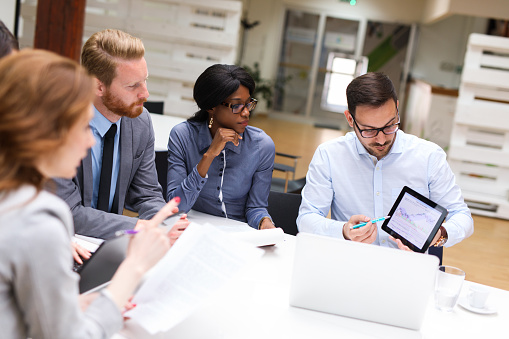 Group of business people is working on new business strategy with a financial analyst while analyzing financial chart during meeting in the office.
