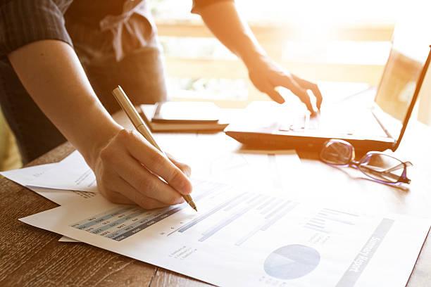 Pessoas de negócio e análise de gráfico gráfico de documento - foto de acervo