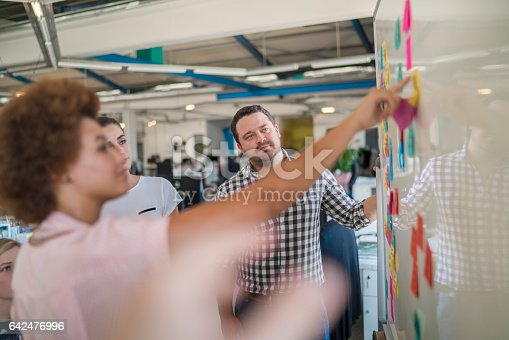 A photo of businessman looking at female colleagues with sticky notes on whiteboard. Professionals are analyzing new strategy. They are in creative office.