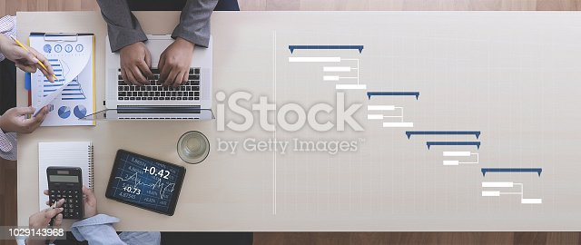 istock Business People Analyzing  PROJECT MANAGEMENT updating Gantt chart 1029143968
