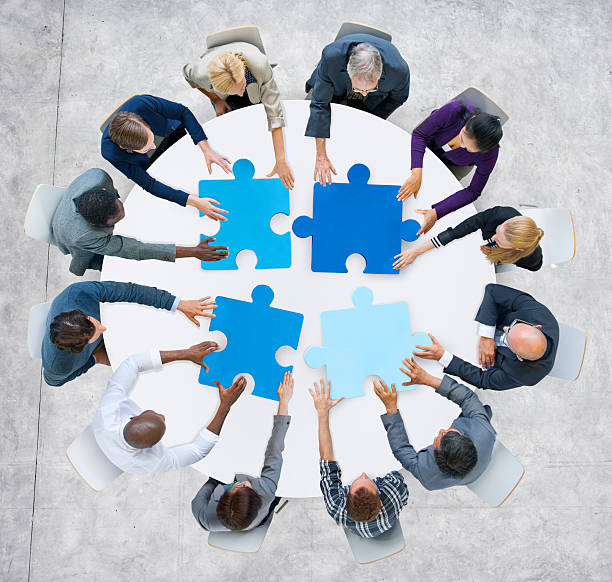 business people and jigsaw puzzle pieces - mergers and acquisitions stock photos and pictures