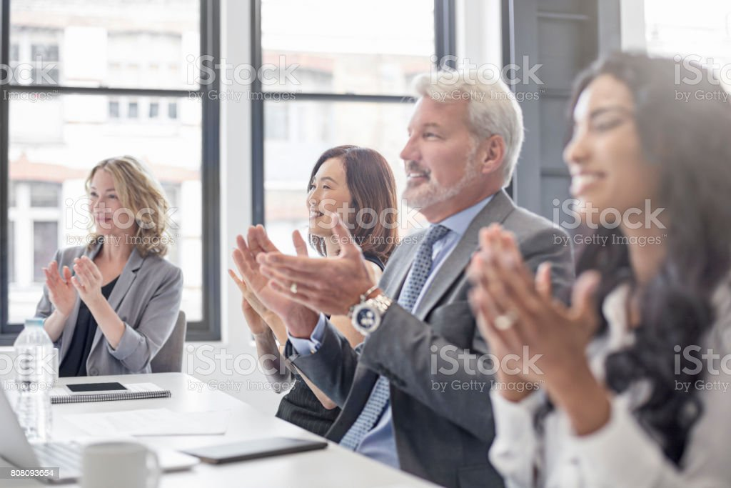 Business people applauding in board room stock photo