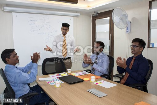 938516440 istock photo Business people applauding manager during a meeting in the office 1185216316