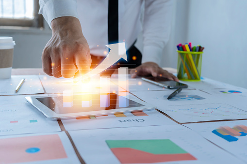 1044507110 istock photo Business people are using a tablet, a rising bar graph. Investment is rising. There is a good trend to invest 1268366310