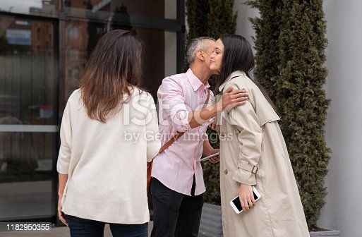 Group of business people arriving at the office and greeting each other with a kiss