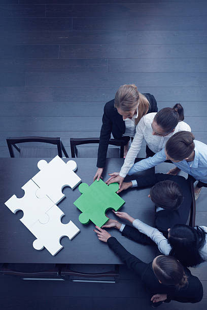 Business people assembling puzzle stock photo
