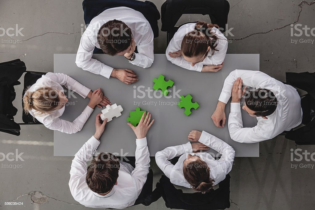 Business people assembling puzzle royalty-free stock photo
