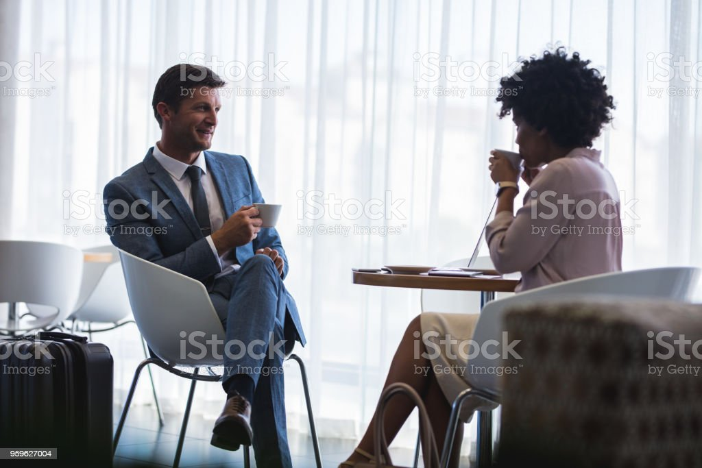 Business people at airport waiting lounge having coffee stock photo