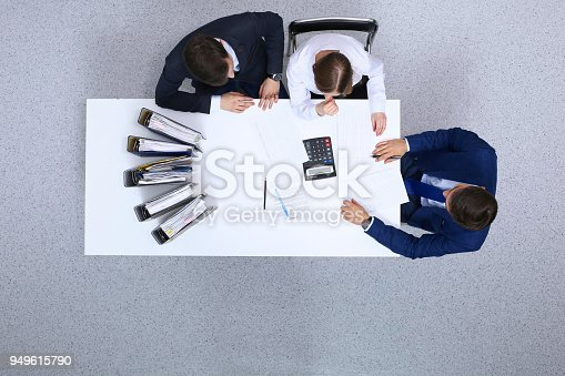 istock Business people at meeting, view from  above. Bookkeeper or financial inspector  making report, calculating or checking balan 949615790