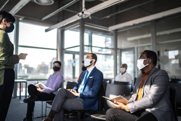 business people attending a seminar with social distancing and face mask - social distancing stock pictures, royalty-free photos & images