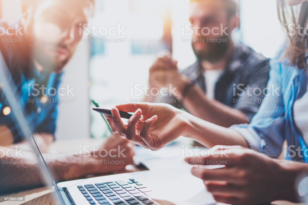 Business people brainstorming concept.Coworkers working at office.Closeup view of female hand pointing on laptop screen. Horizontal, flares effect. stock photo