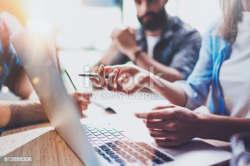 912969272istockphoto Business people brainstorming concept.Coworkers working at office.Closeup view of female hand pointing on laptop screen. Horizontal, flares effect.Blurred background. 912688306