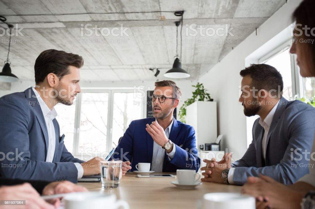 Business people brainstorming idea in meeting Mature businessman explaining strategy to colleagues in meeting. Business people brainstorming idea in office meeting. Adult Stock Photo