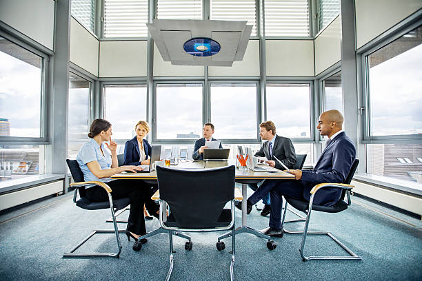 Business people brainstorming in conference room Shot of diverse business people brainstorming in conference room governing board stock pictures, royalty-free photos & images
