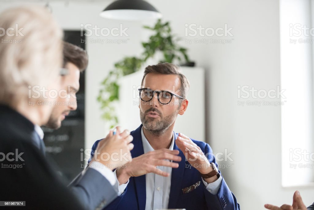 Business people brainstorming in office meeting Mature businessman sharing new ideas to colleagues in meeting. Business people brainstorming idea in office meeting. Adult Stock Photo