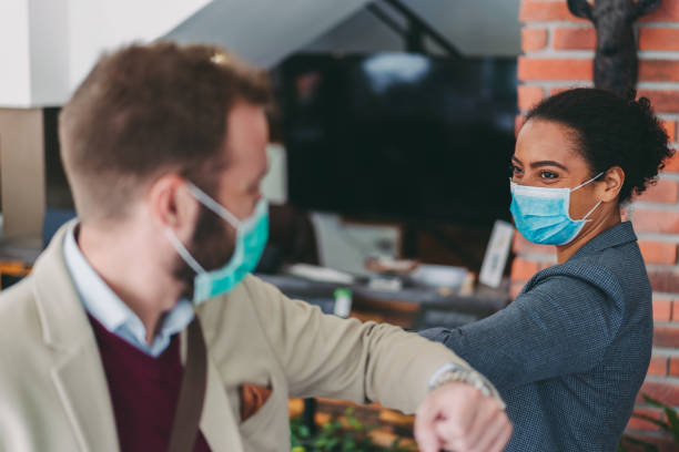 Business people bump elbows as greeting during COVID-19 pandemic stock photo