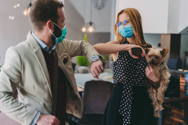 Business people bump elbows in office for greeting during COVID-19 pandemic Colleagues in the office practicing alternative greeting like elbow bump to avoid handshakes during COVID-19 pandemic avoidance stock pictures, royalty-free photos & images