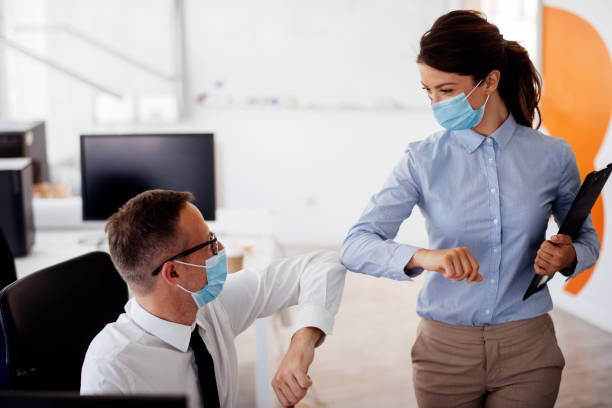Business people bump elbows in office for greeting during COVID-19 pandemic stock photo stock photo