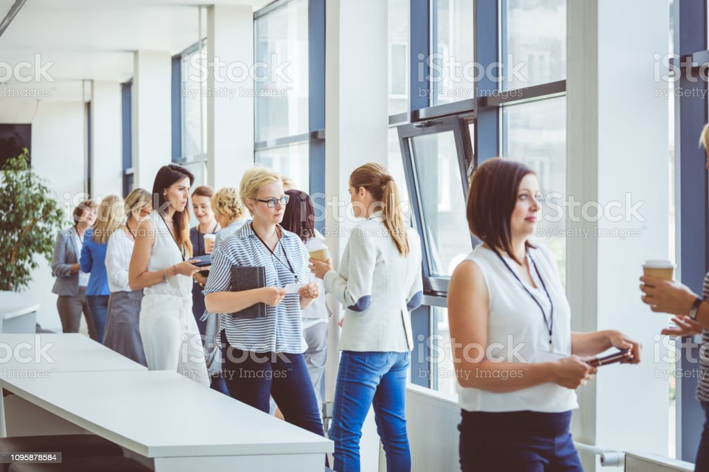 Business people chatting in office lobby during break Group of women talking casually during a break in seminar. Business women chatting in office lobby during break. Adult Stock Photo