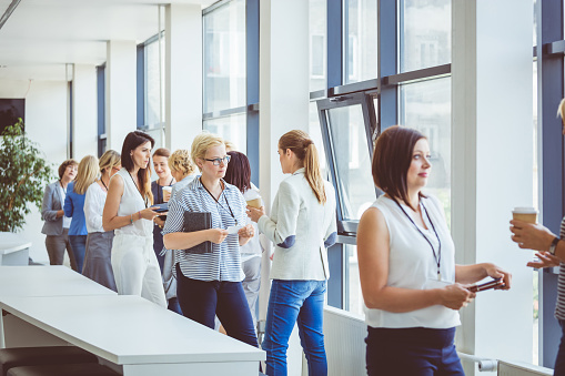 Business People Chatting In Office Lobby During Break Stock Photo - Download Image Now