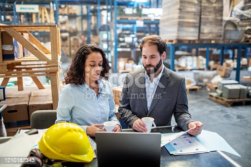 Two business people checking list and inventory on laptop. Businesswoman sharing the stock details with warehouse manager. Both standing at a table with a cup of coffee.