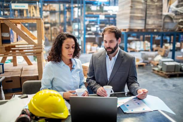 Business people checking list and inventory on laptop at warehouse stock photo
